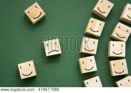 Depression, Mental Health Concept. Sad And Happy Smiles On Wooden Blocks Over Green Background. Top