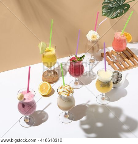 Various smoothie and detox drink on white table. Summer drink concept. Beige wall and White table with sunshine and palm shadow. Smoothie bar menu