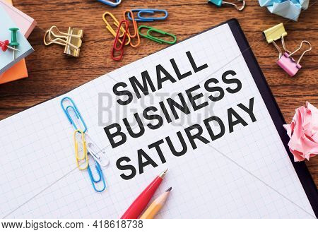 Notepad With The Text Small Business Saturday On The Table With Colored Paper Clips And Crumpled She