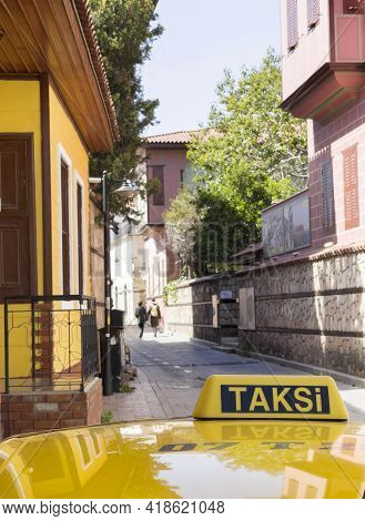 Yellow Taxi Cab Roof Sign With Taksi Turkish Word. Auto Was Parking On The Narrow Old Antalya Street