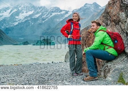 Hiking travel lifestyle. People on hike wearing backpacks in nature landscape with glacier in small icebergs in Tasman Lake on New Zealand in Aoraki Mount Cook national park.