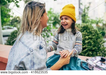 A Happy Little Girl In A Yellow Hat Playing With Her Mom Outdoors. The Cute Kid Has A Joyful Express