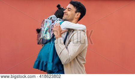 Horizontal Side View Of A Happy Father Hugging His Daughter After The School Day. A Parent Embracing