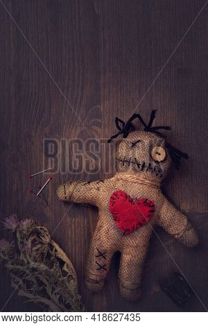 Voodoo doll with pins on a wooden background
