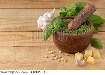 Composition With Italian Pesto Sauce In Clay Mortar And Ingredients On Wooden Table, Copy Space. Tra