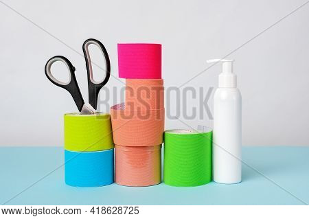 Rolls Of Kinesiology Tape For Athletes, Scissors And Antiseptic Bottle On White Background.