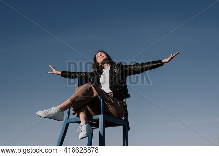 Happy Young Woman In Black Jacket Sitting On Chair With Outstretched Arms Front Of Blue Sky Enjoying