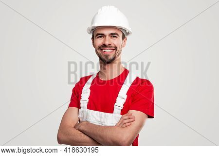 Positive Bearded Male Worker In Red Shirt And White Overall And Hardhat Smiling Friendly And Looking
