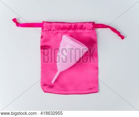 Pink Menstrual Cup And Silk Bag On A White Background. Copy Space