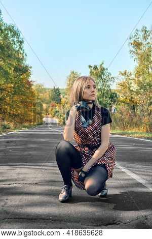 A Girl In A Retro Dress Sits On The Side Of The Road, Next To A Checkered Suitcase. The Girl Looks T