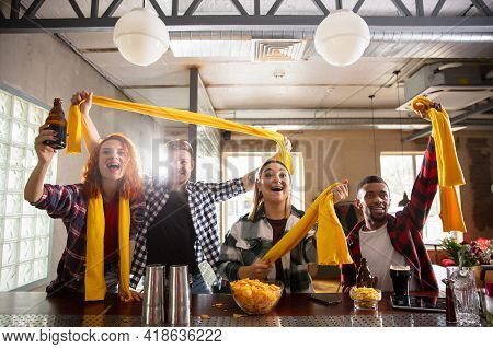 Group Of Friends Watching Sport Match Together. Emotional Fans Cheering For Favourite Team, Watching