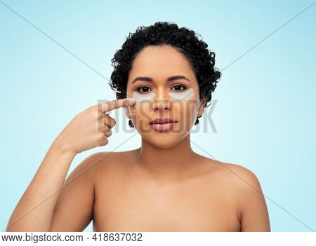 beauty, rejuvenation and people concept - portrait of happy smiling young african american woman pointing to her face with hydrogel under-eye patches over blue background