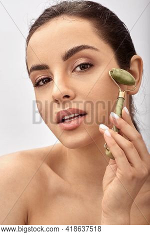 Facial Jade Roller. Young Woman Massages Her Sensuality Face Using A Green Jade Massager Roller For