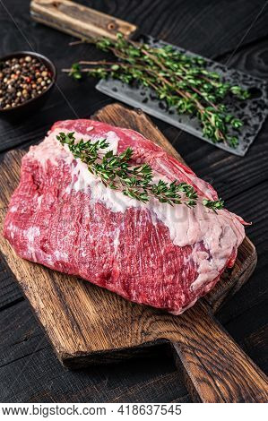 Fresh Raw Round Roast Beef Meat Cut On A Butcher Cutting Board With Cleaver. Black Wooden Background