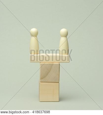 Two Wooden Figures Of A Man On A Swing Made Of Bars. The Concept Of A Dispute Between Opponents, Dia