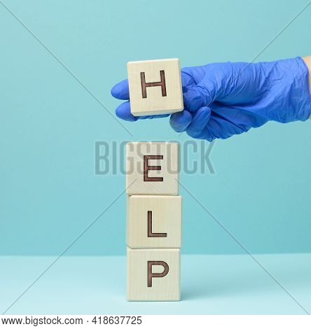 Inscription Help On Wooden Cubes And A Hand In A Blue Medical Glove. First Aid Concept, Answering Qu