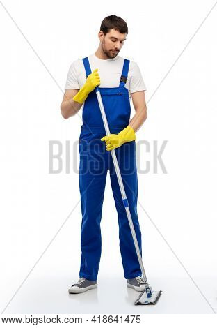 profession, service and people - male worker or cleaner in overal and gloves cleaning floor with mop over white background