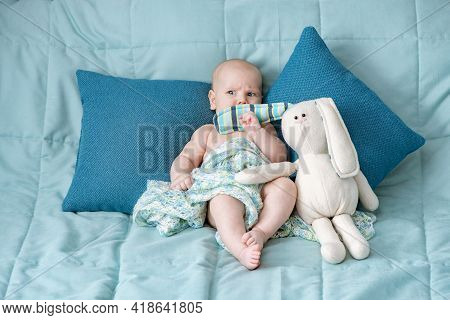 Cute Beautiful Baby Closed Mouth With Hare Toy Ear On Bed. Portrait Of A Child With Emotions