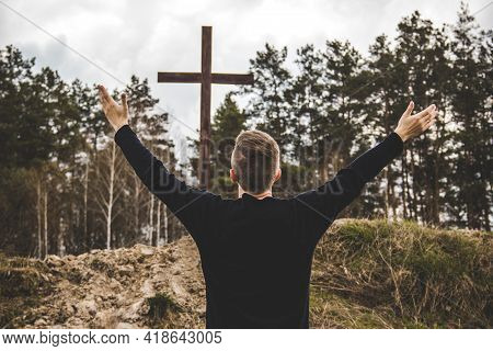 The Man Raised His Hands And Praises God. The Man Looks At The Cross. Man Believes In God. Hope In G