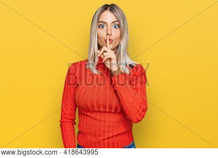Beautiful blonde woman wearing casual clothes asking to be quiet with finger on lips. silence and secret concept.