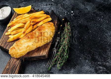 Fish And Chips Dish With French Fries On Wooden Board. Black Background. Top View. Copy Space