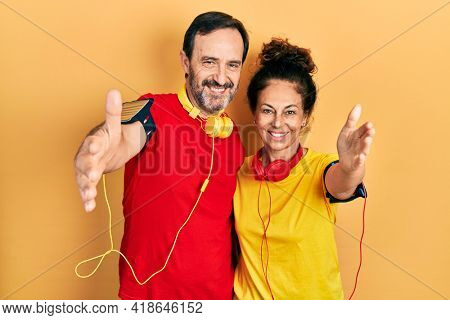 Middle age couple of hispanic woman and man wearing sportswear and arm band looking at the camera smiling with open arms for hug. cheerful expression embracing happiness.
