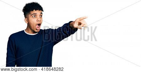Young african american man wearing casual clothes pointing with finger surprised ahead, open mouth amazed expression, something on the front