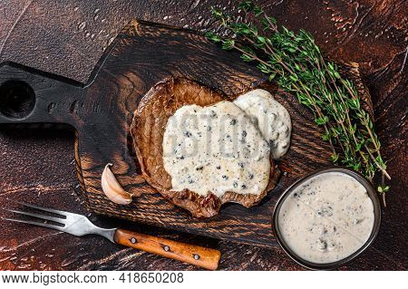 Grilled Sirloin Beef Meat Steak With Peppercorn Sauce. Dark Background. Top View