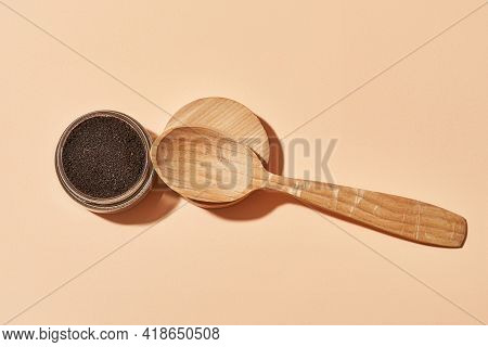 Facial Coffee Scrub In Open Round Can And Wooden Spoon On Light Orange Background, Flat Lay, Top Vie