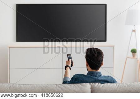 Man Watching Television, Turning On Plasma Flatscreen Tv-set, Pointing Remote Control At Empty Tv Sc