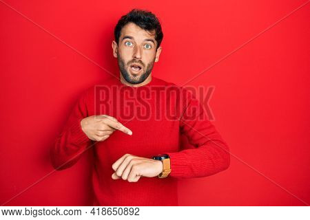 Handsome man with beard wearing casual red sweater in hurry pointing to watch time, impatience, upset and angry for deadline delay