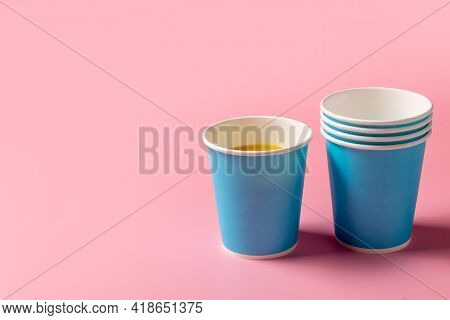 Disposable Paper Cup And Orange Juice On A Pink Background. Disposable Tableware. Disposable Goods.