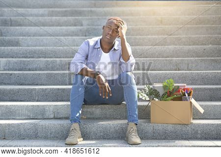 Crisis And Unemployment. Stressed Black Guy With Personal Stuff Sitting On Stairs After Losing His J