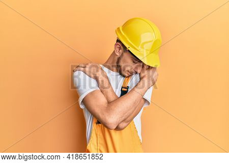 Hispanic young man wearing builder uniform and safety hardhat hugging oneself happy and positive, smiling confident. self love and self care