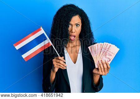 Middle age african american woman holding thailand flag and baht banknotes in shock face, looking skeptical and sarcastic, surprised with open mouth