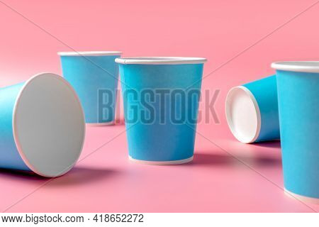 Disposable Paper Cup Randomly And Orange Juice On A Pink Background. Disposable Tableware. Disposabl