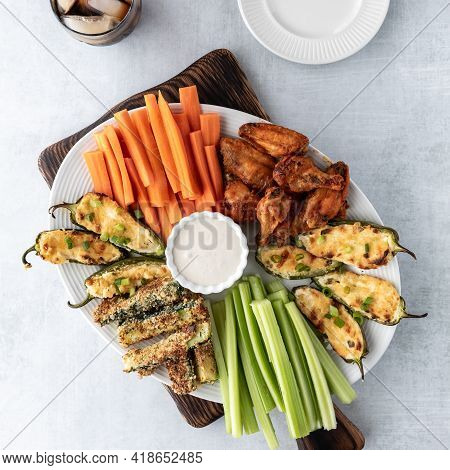 Top Down View Of A Platter Filled With Finger Food Appetizers Including Jalapeno Poppers And Chicken