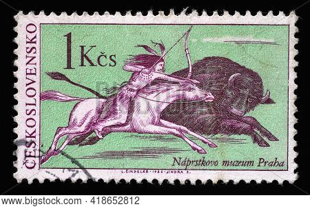 ZAGREB, CROATIA - SEPTEMBER 18, 2014: Stamp printed in Czechoslovakia shows the scene of buffalo hunting, a native American Indian on horseback, pursue a bison galloping, circa 1966