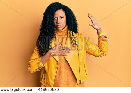 Middle age african american woman wearing wool winter sweater and leather jacket swearing with hand on chest and open palm, making a loyalty promise oath