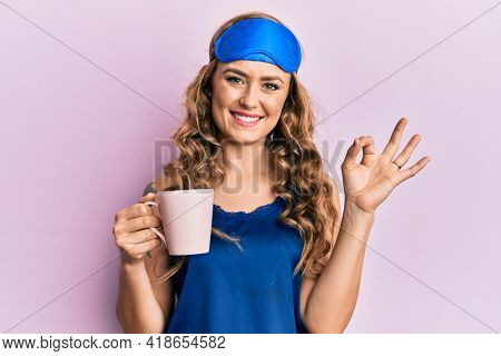 Young blonde girl wearing sleep mask and pyjama drinking coffee doing ok sign with fingers, smiling friendly gesturing excellent symbol
