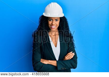Middle age african american woman wearing architect hardhat happy face smiling with crossed arms looking at the camera. positive person.