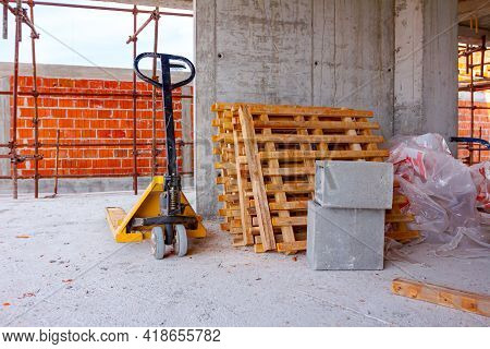 Pallet Jack Or Manually Forklift Used For Delivery And Transport Goods On Pallets Packed In Plastic