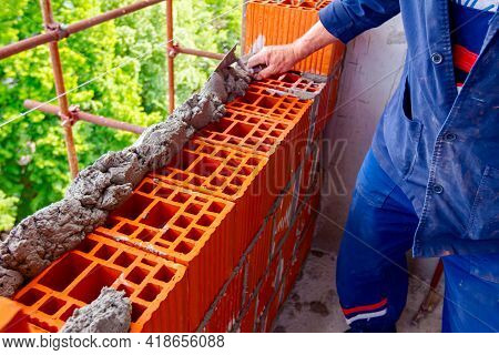 Worker Is Using Spatula, Trowel, To Apply Mortar On Red Blocks To Make Wall, Bricklayer.
