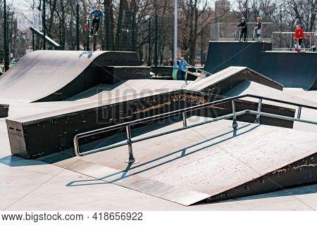 Multiple Obstacles In Outdoor Skatepark In City's Park. Shapes. Rails. Uphills. Downhills. Tricks. E