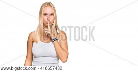 Young blonde girl wearing casual style with sleeveless shirt asking to be quiet with finger on lips. silence and secret concept.
