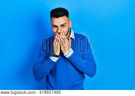 Young hispanic man with beard wearing casual blue sweater laughing and embarrassed giggle covering mouth with hands, gossip and scandal concept