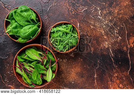 Mix Salad Leafs, Arugula, Spinach And Swiis Chard In Wooden Bowls. Dark Background. Top View. Copy S