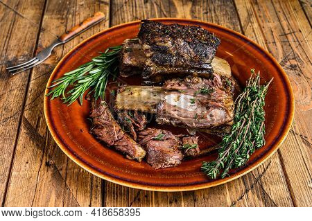 Grilled Short Beef Ribs With Thyme On A Rustic Plate. Wooden Background. Top View