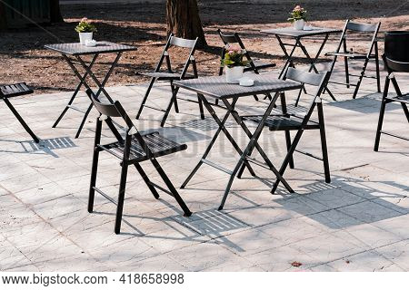 Street Outdoor View Of Old Fashion Cozy Cafe Terrace With Empty Black Iron Chairs And Tables In Summ