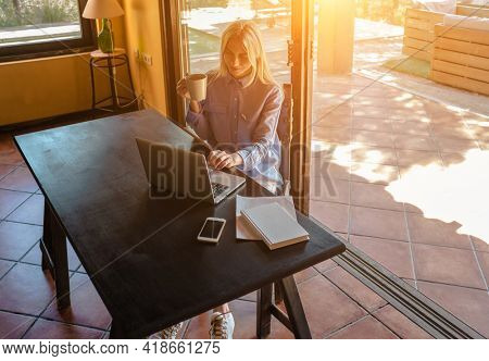 Working from home. Woman talking on video call with Family, using smartphone and drinking tea. Online chat. Spend free time on terrace. Staying connected, Social distancing, internet. Work life.
